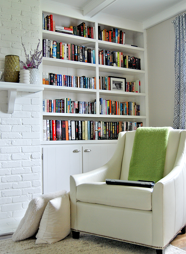 simple-home-library-design-for-small-space-with-wall-bookshelves-built-in-white-painted-cabinets-using-solid-brushed-cup-pulls-handle-and-white-leather-wingback-chair-on-grey-rug
